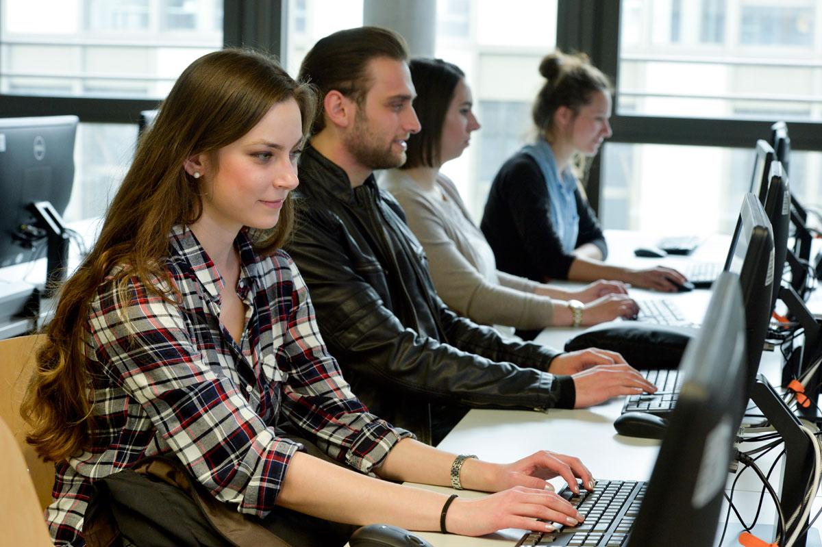 Vier Personen sitzen an einer Tischreihe vor Bildschirmen und arbeiten