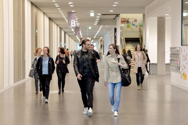 Student/innen laufen über den Universitätsflur